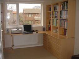 A full view of the corner desk and bookcase